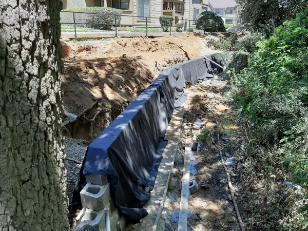 Retaining wall and French drains under construction.