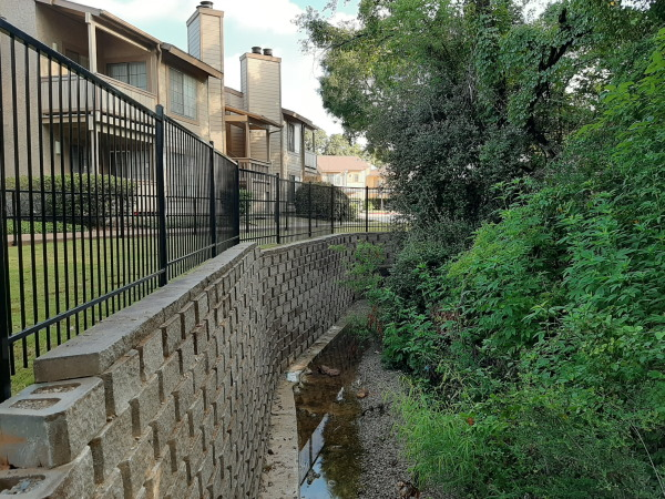 The finished project: Retaining wall, French drains, safety fence and turf create an inviting area along the creek's edge.